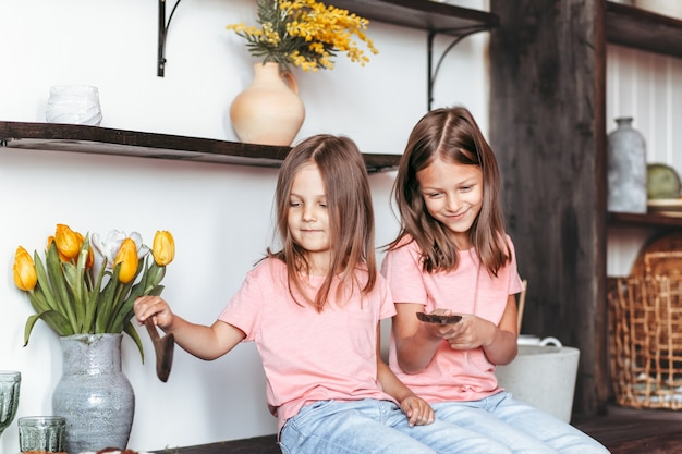 Due ragazze giocano in cucina. le sorelle felici si siedono insieme