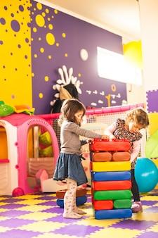 Due ragazze giocano con dei grandi mattoncini nella stanza dei giochi