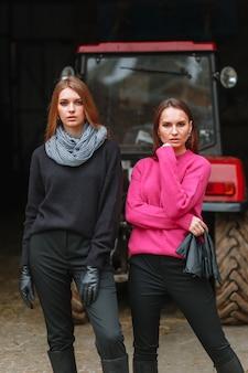 Due ragazze in posa accanto a un trattore