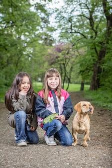 Due ragazze in posa con un cane