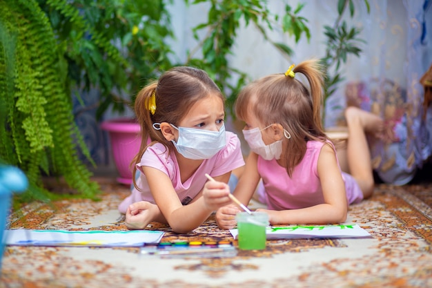Due ragazze in maschere mediche protettive dipingono con vernici sdraiato sul pavimento a casa