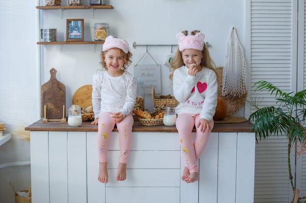 Due ragazze in pigiama in cucina dopo aver dormito bevono latte a casa