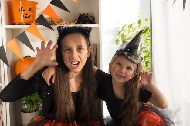 Due ragazze sorelle di dieci e sette anni in costumi da strega su halloween celebrano la vacanza a