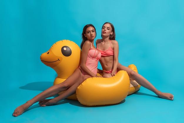 Due ragazze in costume da bagno che posano sull'anatra gonfiabile sulla parete blu