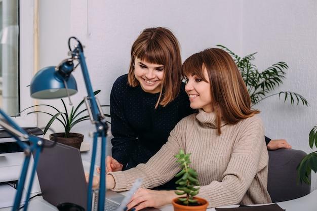 Due gemelli di ragazze lavorano fianco a fianco in ufficio su un laptop. interazione di sorelle e colleghi al lavoro. la psicologia dei rapporti di lavoro.