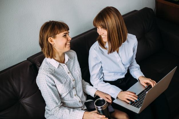 Due gemelli di ragazze lavorano fianco a fianco in ufficio su un laptop. interazione di sorelle e colleghi al lavoro.