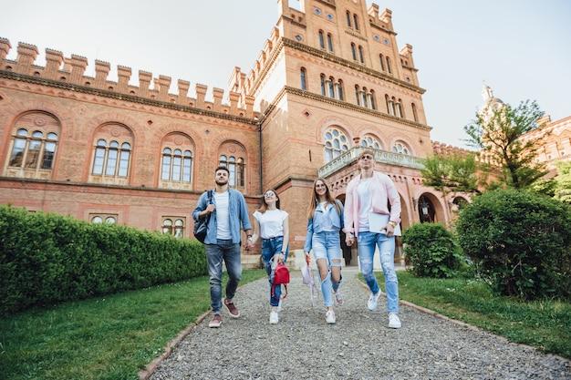 Due ragazze e due ragazzi si tengono per mano e camminano per il campus.