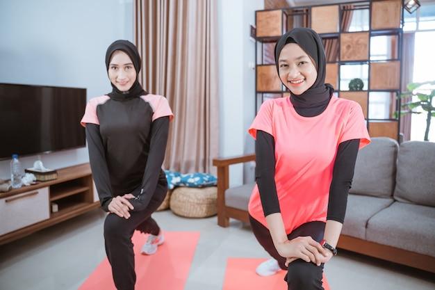 Due ragazze che indossano un velo sorridono mentre fanno movimenti di affondi mentre si esercitano insieme al chiuso a casa