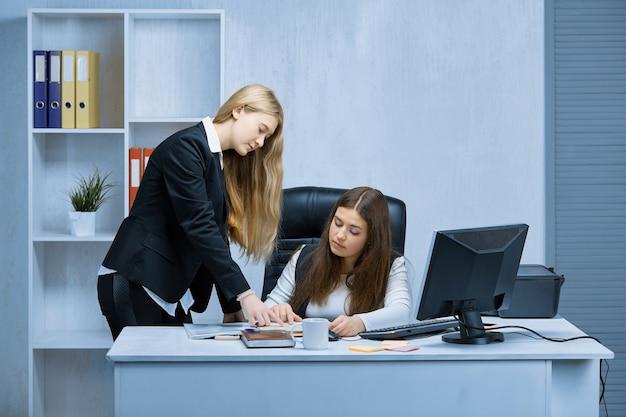 Due ragazze a una scrivania bianca in ufficio si consultano durante l'esame di un progetto comune