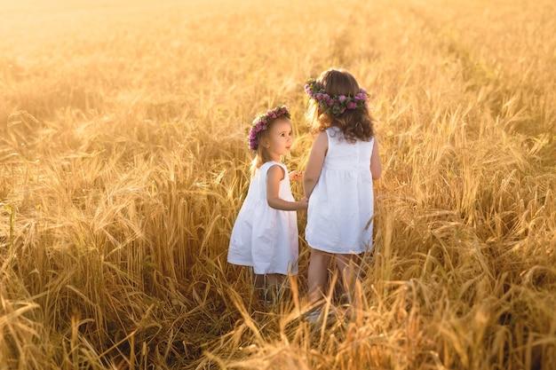 Due ragazze in abiti bianchi camminano mano nella mano in un campo di grano.