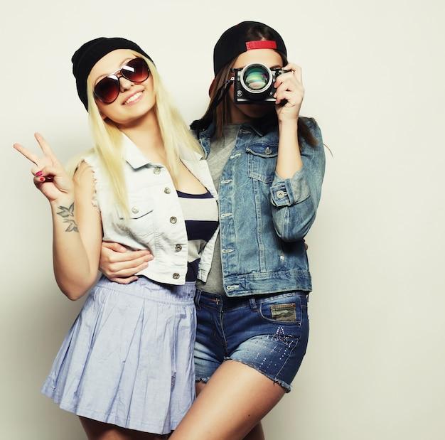 Due ragazze con telecamere in stile hipster su sfondo grigio