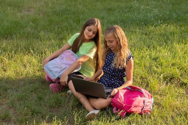 Due ragazze con laptop e valigette che fanno i compiti o si divertono seduti sull'erba fuori