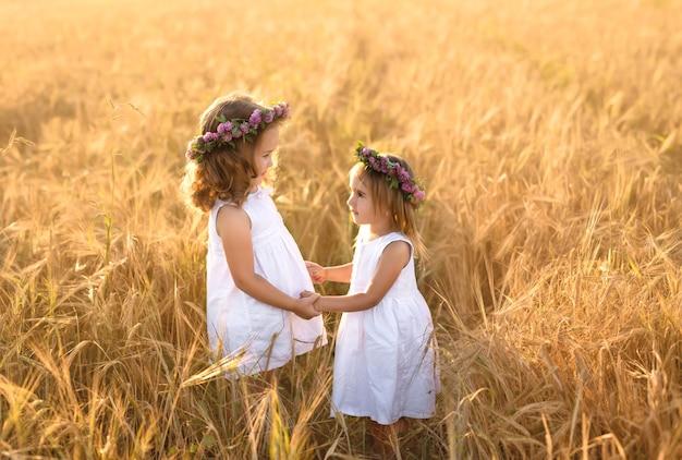 Due ragazze con ghirlande di trifoglio si tengono per mano in un campo di grano al tramonto.