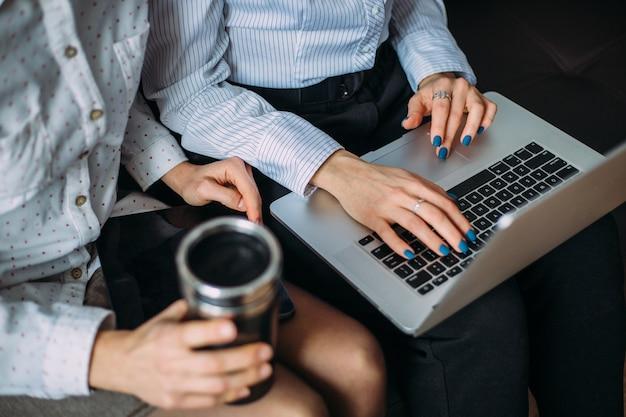 Due ragazze lavorano fianco a fianco in ufficio su un laptop. interazione dei colleghi al lavoro.