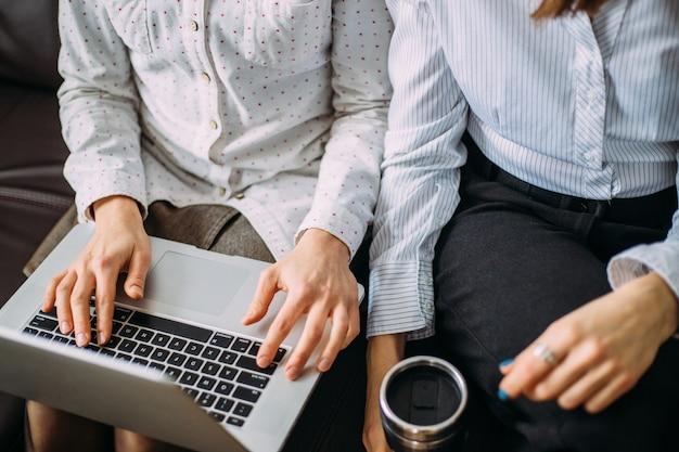 Due ragazze lavorano fianco a fianco in ufficio su un laptop.