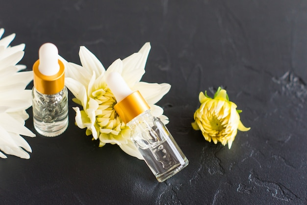 Due bottiglie di vetro di contagocce per uso medico e cosmetico su sfondo nero con fiori bianchi.