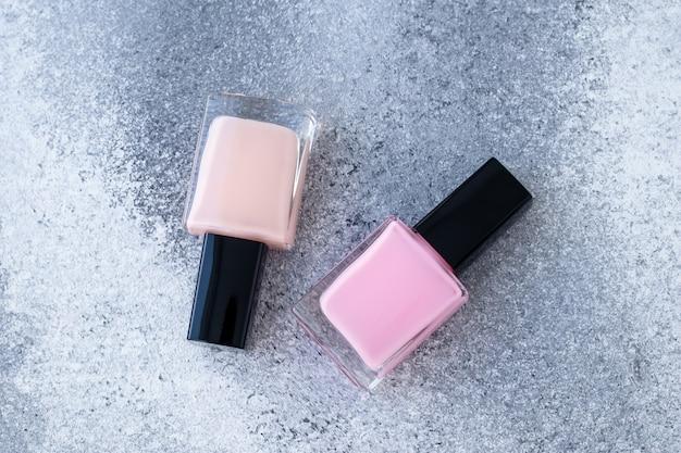 Due bottiglie di vetro di smalto. smalto beige e rosa neutro su sfondo grigio. Foto Premium