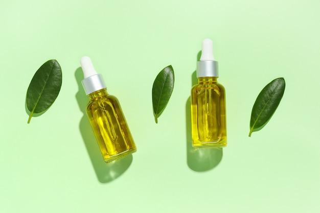 Due bottiglie di vetro con olio di bellezza naturale e foglie verdi con ombre su sfondo verde