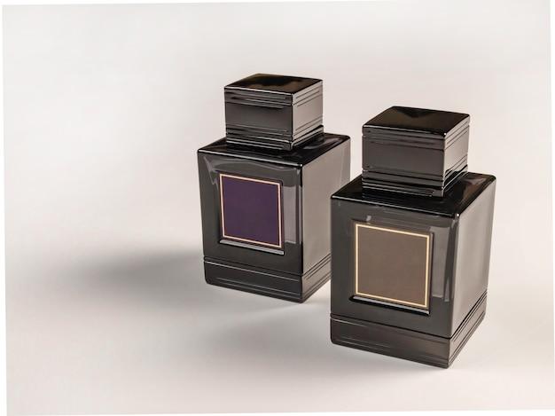 Due contenitori in vetro con coperchi in plastica nera su sfondo chiaro. industria della profumeria. copia spazio a sinistra