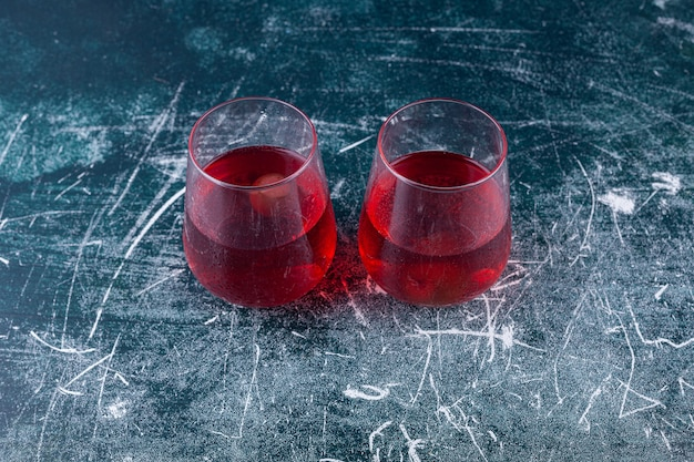 Due tazze di vetro di succo di frutta fresco poste su un colorato.