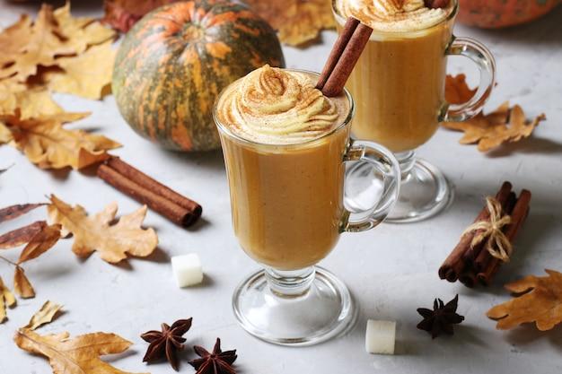 Due tazze di vetro zucca latte con spezie e schiuma cremosa su sfondo grigio con zucche e foglie d'autunno. avvicinamento.