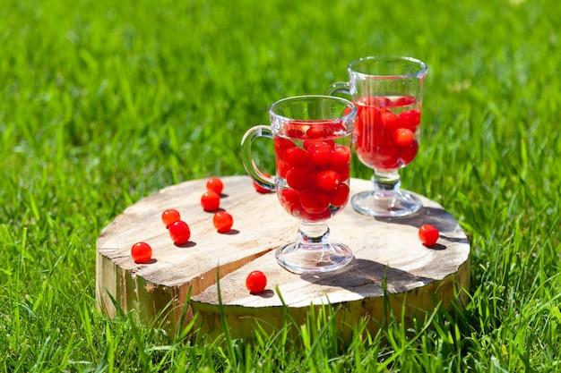 Due bicchieri di vetro con bacche di ciliegia e acqua stanno su un supporto di legno con una crepa sul prato verde in una soleggiata giornata estiva.