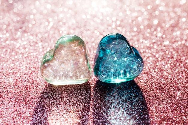 Due cuori di vetro, verde chiaro e blu sullo sfondo sfocato di glitter rosa. le luci risplendono attraverso i cuori trasparenti.