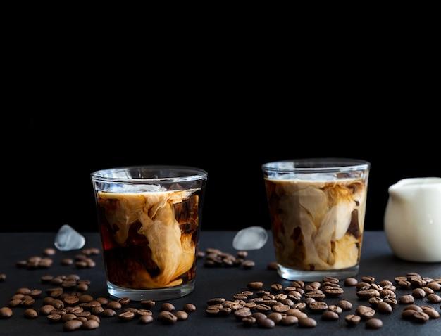 Due bicchieri di caffè ghiacciato con cubetti di gelato alla crema e chicchi di caffè su sfondo scuro con spazio di copia