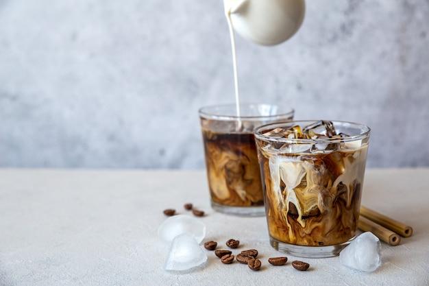 Due bicchieri di caffè ghiacciato con crema che versa dall'alto e chicchi di caffè