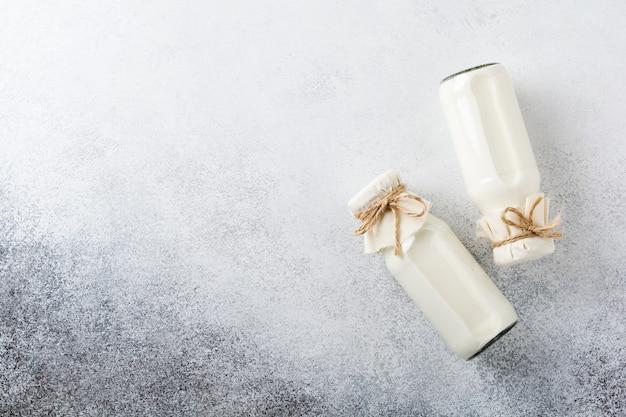 Due barattoli di vetro di latte su un cemento grigio. concetto di prodotti lattiero-caseari.