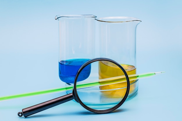 Due misurini di vetro con liquido giallo e blu e una capsula di petri sotto una lente d'ingrandimento su uno sfondo azzurro. tubi e attrezzature da laboratorio. il concetto di esperimenti di laboratorio.
