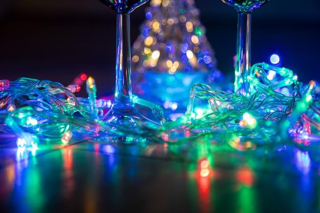 Due bicchieri sullo sfondo di un brillante albero di natale e una ghirlanda multicolore su uno sfondo notturno scuro. festa di capodanno...