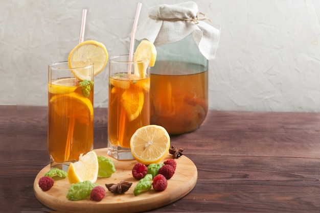 Due bicchieri e banca con kombucha e fette di limone e lamponi su un tavolo di legno.
