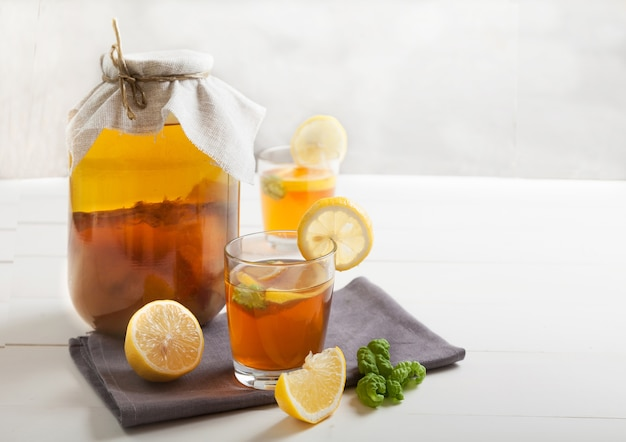Due bicchieri e banca con kombucha e fette di limone su un tavolo bianco