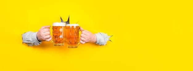 Due bicchieri di birra in mano, bicchieri tintinnanti Foto Premium