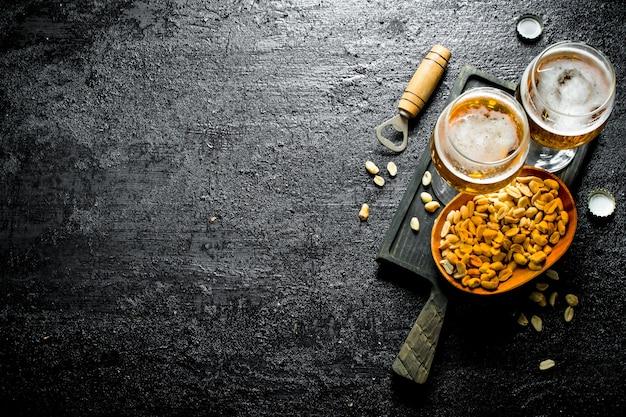 Due bicchieri di birra e arachidi in una ciotola su un tagliere nero sul tavolo rustico