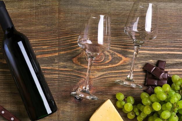 Due bicchieri, bottiglia di vino rosso e uva su un tavolo di legno. vista dall'alto. copia spazio. disposizione piatta. natura morta