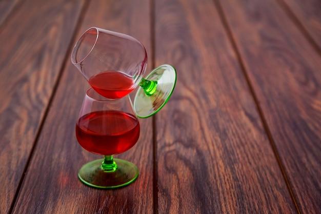 Due bicchieri di brandy o cognac e bottiglia sul tavolo di legno.