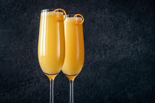 Due bicchieri di cocktail buck's fizz sul tavolo nero