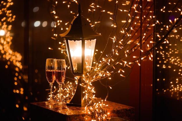 Due bicchieri di champagne su macchie di sfocatura sullo sfondo delle luci. concetto di celebrazione, spazio libero per il testo