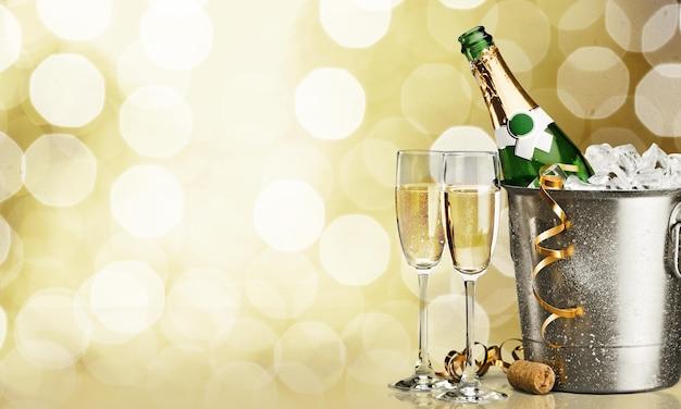 Due bicchieri di champagne e una bottiglia sullo sfondo