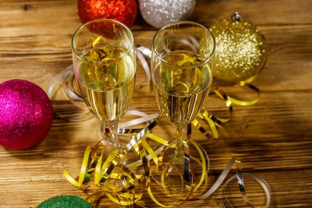 Due bicchieri di champagne e decorazioni natalizie festive sul tavolo di legno. festa di natale e capodanno
