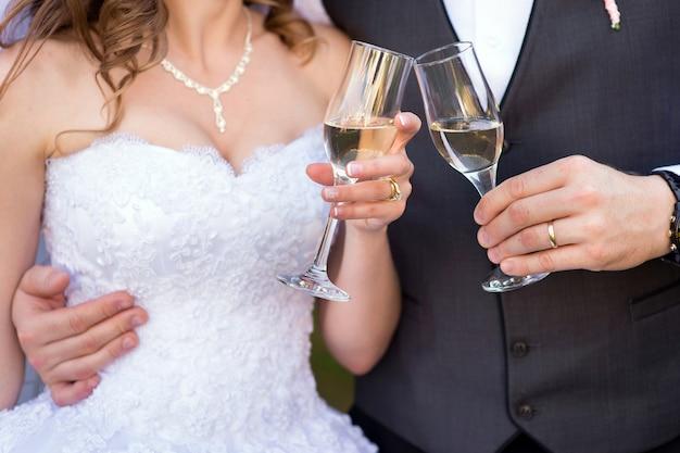 Due bicchieri di champagne nelle mani della sposa e dello sposo