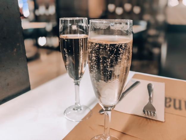 Due bicchieri di champagne su un tavolo in un ristorante. concetto di celebrazione del nuovo anno. fotografia di champagne.