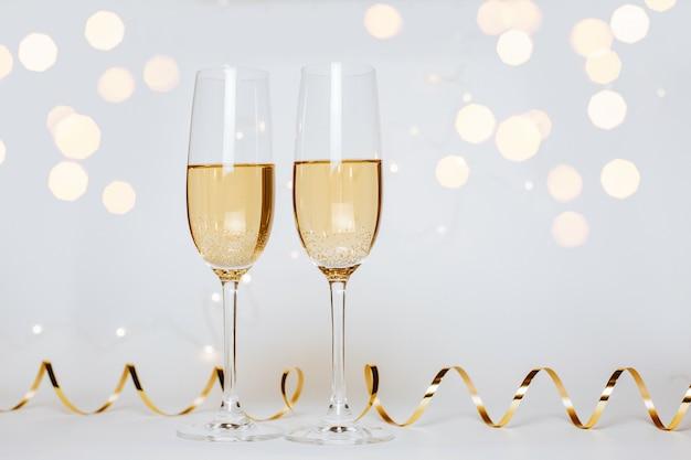 Due bicchieri di champagne con luci e nastri su una vacanza di sfondo bianco