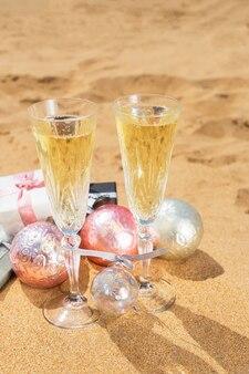 Due bicchieri di champagne e bollicine natalizie con regali e decorazioni natalizie sulla spiaggia
