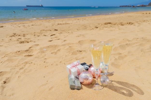 Due bicchieri di champagne natalizio con bollicine e scatole regalo natalizie e decorazioni sulla spiaggia