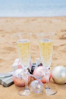 Due bicchieri di champagne natalizio con bolle regali di natale e decorazioni sulla spiaggia in riva al mare