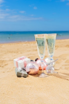 Due bicchieri di champagne natalizio con scatole regalo natalizie e decorazioni sulla spiaggia in riva al mare
