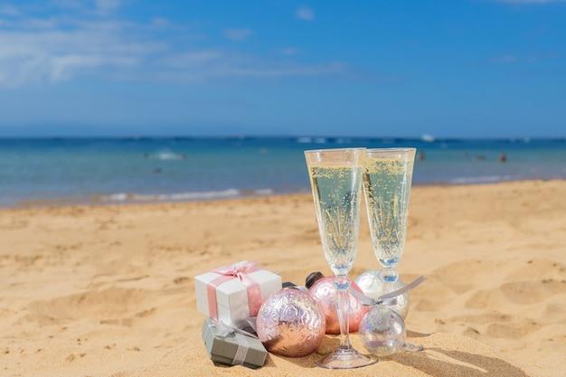 Due bicchieri di champagne natalizio con scatole regalo natalizie e decorazioni sulla spiaggia